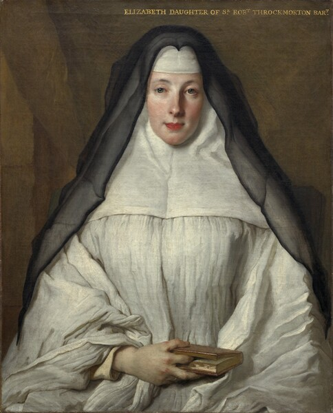 """Seen from about the lap up, a woman with light skin, wearing a voluminous, dress-like garment that covers her head and forehead beneath a black veil that falls over and past her shoulders, sits facing us in this vertical portrait painting. The light falls across her from our left, illuminating her smooth, alabaster skin and flushed cheeks. She looks at us steadily with gray eyes under gently arched brows. Her coral-pink lips are closed and possibly pulled back slightly at the corners. Her garment is pleated across the chest and sleeves to fall in full folds over her arms. A wide panel covers her shoulders, sides of her neck, and head, and a white band is pulled down over her forehead. The semi-transparent black veil creates a stiff peak over her head where it attaches to the top of this garment, called a wimple. Her right hand, on our left, rests in her lap and her index finger marks her spot in the small book she holds. The other hand is presumably tucked under the folds of her garment. The background behind her is peanut-brown, and a diagonal line suggests a curtain pulled to our right. An inscription in all-capital, gold letters spans the right half of the painting along the top edge: """"ELIZABETH DAUGHTER OF SR ROBT THROCKMORTON BART."""""""