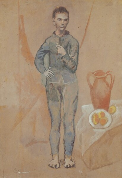 """A pale, gray skinned young man stands next to a vase and plate of food against a pinkish-tan background in this loosely painted vertical painting on cardboard. The man's body faces us but he looks down and slightly to our right with deeply shadowed eyes under dark brows. He has close-cropped, dark brown hair, a straight nose, and his full mouth is closed. He wears a slate blue, fitted jacket over leggings, both painted with smudges of gray, dark green, and lilac purple, and some areas of the tan background show through. His feet are bare. The man's left elbow, on our right, is bent so he holds his hand at his chest. His opposite fingers splay over his hip. Loosely painted and indistinct, a box-like form next to the man's feet seems to be draped with a translucent white cloth. The box or table holds a tall terracotta vase behind a white dish. Four oval-shaped objects, painted with marigold orange and buttercup yellow, fill the plate and another sits on the cloth next to the dish. Sweeping but vague coral-peach lines and washes on the background suggest that the man may stand in front of a curtain. The artist signed the work """"Picasso"""" in the lower left."""