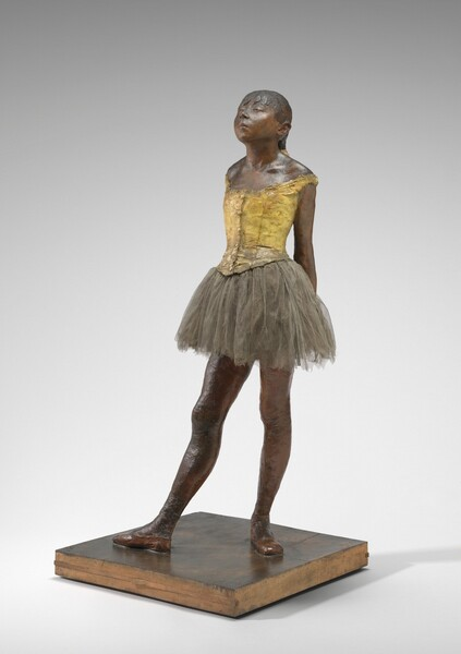 Sculpted with rich brown wax, a young ballerina stands with her arms straight, hands clasped behind her back, and one foot in front of the other on a square wooden base. Her body is angled to our left in this photograph. Both feet are splayed outwards and her right foot is placed far in front of her left. Bangs cover her forehead, and she has a heart-shaped, upturned face with a squat nose and slightly pursed lips. Her heavy-lidded eyes are nearly closed and her hair is pulled back and tied with a wide, cream-colored ribbon. She wears a fabric costume with a sleeveless, gold-colored bodice, a gray tulle skirt, and ballet slippers. Her body is sculpted from dark brown wax and a layer of wax covers her hair, bodice, and ballet slippers.