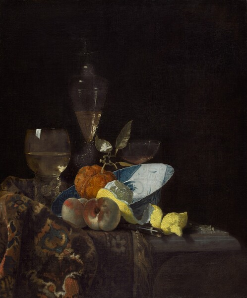 A blue-and-white porcelain bowl, fruit, wine glasses, and a woven rug are gathered on a tabletop in front of a black background in this vertical still life painting. Light strongly illuminates the objects, creating a stark against to the dark background. At the center of the composition, the porcelain bowl is tipped so its wide brim rests on the rug bunched on the tabletop to our left. The rug is painted with a pattern in earthy beige and chocolate brown, denim blue, bronze, and cream. A piece of roughly textured orange fruit resembling a tiny pumpkin has a stem with a small white blossom growing from its top. The fruit sits in the bowl alongside a vivid yellow lemon that has been partially peeled. The top has been cut from the lemon to form a long strip that curls onto the table, and the pulp glistens in the light. Two peaches sitting in front of the bowl are painted with tones of silvery ivory and burnt orange. The handle of a utensil juts out from between the peaches and lemon peel. Three glasses are arranged in a row behind the fruit and bowl. The glass to the left has a round bowl over a thick, columnar stem and a tall, gently flaring glass behind the orange fruit are both half-filled with pale gold liquid. A glass with a wide, shallow, scalloped-edged bowl is mostly hidden behind the bowl, to our right.