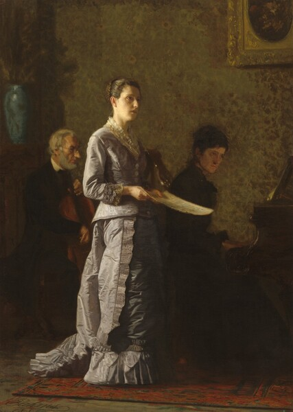 A woman with dark hair pulled up in a bun, wearing a long, lilac-colored silk dress, stands singing in front of woman playing a piano and a man playing a cello in this vertical painting. All the people have pale skin. Light falls from our left onto the singing woman and the musicians sit in shadow behind her. The singing woman's body is angled to our right, almost in profile, and she looks up and off into the distance with the light illuminating the curve of her forehead and right cheek. She has dark eyes, an oval face, and her lips are parted. She holds a sheet of paper, presumably music, down at her waist. Her pale purple dress is edged with lace at the neck and cuffs. A ruffle runs down the side of her floor-length skirt, and a ruffle lines the bottom hem around her feet. A train affixed to the back of the dress rests on the floor behind her. Both musicians face our right in profile. To our left, the man playing the cello has a white beard and hair, and he wears a dark suit and glasses. To our right, the woman at the piano has dark hair pulled up and she wears a dark dress. The singing woman stands on a brick-red, patterned area rug and the wall behind her is papered with a sunflowers and perhaps leaves against a gold and caramel-brown background. A tall, light blue vase sits on a mantlepiece along the left edge, next to the cello player. A gold-framed picture hangs on the wall over the pianist.