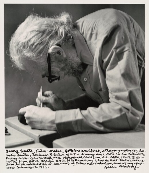Harry Smith, Film-maker, folklore archivist, ethnomusicologist, hermetic painter, alchemist & Bishop of O.T.O. erasing some note in his calendar, Packing boxes of books and rare phonograph records in his room prior to departure from Hotel Breslin 28th St. & Broadway where he lived several years. Some boxes were stored in basement of Film-Maker