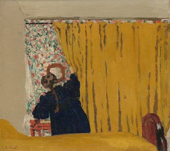 """A woman pushes aside a deep golden yellow curtain that fills three-quarters of this nearly square painting. The curtain runs on a rod parallel and close to the top of the canvas, extends off the right edge, and falls behind a bed covered in the same color. The bed in the foreground is cropped by the left edge of the painting and the brown, arched wood footboard almost reaches the right side. The woman stands on the opposite side of the bed, facing away from us as she pulls at the curtain with her right hand. She wears a navy blue dress and a brown braid falls down her back. She reveals an area covered in a pink, green, and white floral pattern that seems to match the size of the curtain, but it is hard to tell if this is another curtain or wallpaper behind the yellow curtain. A round mirror hangs on the floral patterned area above a red piece of furniture, perhaps a small table or stool. The wall around the patterned area and curtain is painted ivory. The paint is loosely applied so brushstrokes are visible throughout, especially in the floral pattern. The artist's signature, """"E. Vuillard"""" is painted in red in the lower left corner."""