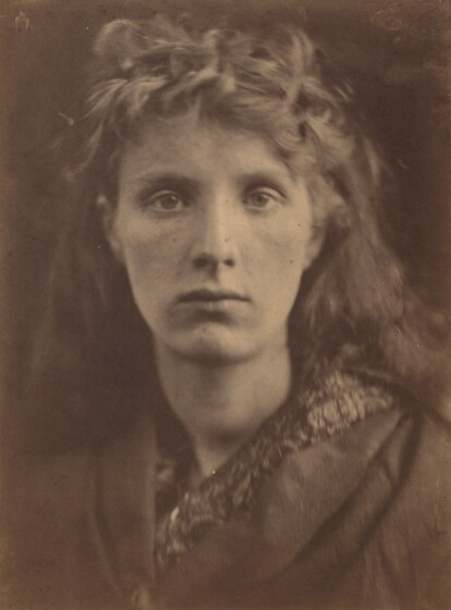 The head and shoulders of a young woman with pale skin and long hair nearly fill this vertical, sepia-toned photograph. Shown against a dark background, she looks directly at us. Her nose is straight and her lips closed. Wavy curls piled over her forehead suggest that her hair is partially pulled back or pinned up around her oval face, and it falls behind her shoulders. Her garment has wide lapels like an old-fashioned coat, and is worn over patterned clothing.
