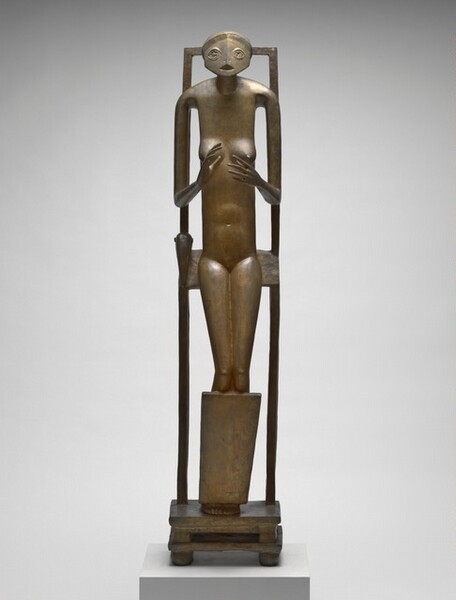 An abstracted, thin, nude woman with a rounded face seems to half-sit, half lean back against a tall, narrow chair in this golden, bronze sculpture. Her body faces us in this photograph. Her wide, oval face has two stylized, star-like eyes and a triangular opening for a mouth. The torso is tall and thin, and her limbs elongated. With thin arms, she holds up open hands with palms facing each other at the level of her round breasts. Her fingers are long and delicate. She is encased within a tall, rectangular frame. With knees slightly bent and seeming to rest against a panel that runs in front of her shins, she seems to lean against a slat against her backside, perhaps the seat to the stylized chair. Her feet are pressed together on a double-tiered, low, square base with four square feet at the corners.