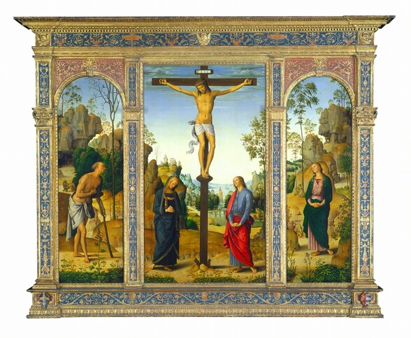 One tall, rectangular panel is flanked by arched panels to each side, all set within a carved, painted, gilded wooden frame. The central panel shows two people at the foot of a wooden cross, to which a man is nailed, and the panels to each side are each occupied by a single person. All the people have pale skin and are shown against landscapes with rocky outcroppings along a river that extends into the deep distance. At the center of the middle panel, the man hangs from the cross from nails in his hands and one nail driven through his overlapping feet. He is nude except for the white loincloth wrapped around his hips, which falls in fluttering ripples alongside his right leg, on our left. Blood drips down his forehead from where a ring of thorns encircles his shoulder-length, chestnut-brown hair. His head tilts to his right, our left, and his eyes are closed or downcast. Blood also drips from his hands and feet, and from a slit over his right ribcage. The woman standing to our left of the cross wears a navy-blue robe edged in gold that covers her head and drapes to her ankles above bare feet. Her head tips down to our right, and she holds her hands clasped loosely, fingers intertwined, at her waist. The person standing to our right of the cross wears a cobalt-blue robe under a vivid, scarlet-red cloak. He has blond curly hair and delicate features, like the woman. With arms nearly straight, he holds his interlaced fingers with palms facing down, close to his body. He looks up at the man on the cross. Low hills dotted with flowers and plants separate the people from a river that runs between rocky hills and outcroppings. Stone buildings line the bank beyond a bridge spanning the river in the distance, and three boats sail near the horizon line, which comes halfway up the composition. The hills and mountains look green and then blue in the deep distance under a sky that fades from nearly white along the horizon to pale, topaz-blue along the top edge of the panel, whic