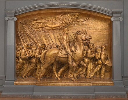 "A white man in military uniform rides a horse in front of a regiment of five rows of Black troops in this sculpture, which is painted entirely in gold. The artist created a shallow, stage-like space with an arched top so the men are sculpted in three dimensions, though they become more compressed as they move back in space. The men and horse face our right in profile in this view. The man on the horse has a pointed, straight nose and a goatee. He wears a cap with a flat top and narrow brim, a knee-length coat, gloves, and knee-high boots with spurs. He holds a thin sword down by the side of the horse with his right hand and holds the reins of the horse with his left. The horse's head is pulled upwards by the short reins and its mouth is open around the bit. About twenty soldiers are lined up in rows behind the horse and march in unison. They carry blankets rolled atop knapsacks, canteens, and rifles resting on their right shoulders. However, the details of how their uniforms bunch up around their equipment and the way their caps have been molded and fit is unique to each person. Their ages also vary from young, cleanshaven individuals to bearded older men. Two men carry furled flags near the back, to our left, and a drummer boy plays at the head of the regiment, to our right. All the men look straight ahead, their lips closed. A female figure in a billowing robe floats above them under the arched top with her eyes closed. Her left arm is outstretched and she holds a laurel branch and poppies close to her body with her right arm. An inscription in the upper right corner is created with raised capital letters: ""OMNIA RELINQVIT SERVARE REMPVBLICAM."" A longer inscription is carved into the base along the bottom edge of the memorial, also in all caps: ""ROBERT GOVLD SHAW KILLED WHILE LEADING THE ASSVLT ON FORT WAGNER JVLY TWENTY THIRD EIGHTEEN HVNDRED AND SIXTY THREE."" The artist's signature is inscribed In the lower right corner, in smaller letters: ""AVGVTVS SAINT GAVDEN M-D-C-C-C-L X X X X V I I I."""