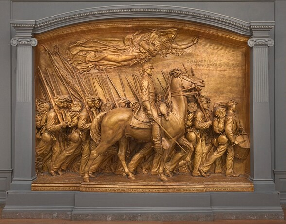 """A white man in military uniform rides a horse in front of a regiment of five rows of Black troops in this sculpture, which is painted entirely in gold. The artist created a shallow, stage-like space with an arched top so the men are sculpted in three dimensions, though they become more compressed as they move back in space. The men and horse face our right in profile in this view. The man on the horse has a pointed, straight nose and a goatee. He wears a cap with a flat top and narrow brim, a knee-length coat, gloves, and knee-high boots with spurs. He holds a thin sword down by the side of the horse with his right hand and holds the reins of the horse with his left. The horse's head is pulled upwards by the short reins and its mouth is open around the bit. About twenty soldiers are lined up in rows beyond the horse, and they march in unison. They carry blankets rolled atop knapsacks, canteens, and rifles resting on their right shoulders. However, the details of how their uniforms bunch up around their equipment and the way their caps have been molded and fit is unique to each person. Their ages also vary from young, cleanshaven individuals to bearded older men. Two men carry furled flags near the back, to our left, and a drummer boy plays at the head of the regiment, to our right. All the men look straight ahead, their lips closed. A female figure in a billowing robe floats above them under the arched top with her eyes closed. Her left arm is outstretched and she holds a laurel branch and poppies close to her body with her right arm. An inscription in the upper right corner is created with raised capital letters: """"OMNIA RELINQVIT SERVARE REMPVBLICAM."""" A longer inscription is carved into the base along the bottom edge of the memorial, also in all caps: """"ROBERT GOVLD SHAW KILLED WHILE LEADING THE ASSVLT ON FORT WAGNER JVLY TWENTY THIRD EIGHTEEN HVNDRED AND SIXTY THREE."""" The artist's signature is inscribed In the lower right corner, in smaller letters: """"AVGVTVS SAINT """