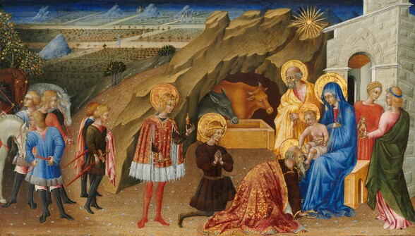 Three men with crowns and wearing gold-trimmed robes stand and kneel before a woman sitting on a wooden, box-like seat holding a baby to our right, in front of a rocky cave and landscape, in this horizontal painting. A balding man with a gray beard and hair, Joseph, and two younger people with blond hair stand around the woman, Mary, to our right, and a group of five young men or boys and three horses gather near the left edge. All the people have pale skin. Mary, the baby Jesus, Joseph, and the three men paying homage, the magi, all have shimmering gold halos. One balding magi with a long white beard kneels and kisses the baby's feet. He wears a gold and crimson-red brocade-like robe over a burgundy-red garment, and he holds a pointed gold crown in his right hand, which rests on the ground. Behind him and to our left, a younger magi with curly blond hair and goatee, wearing a wine-red tunic belted with gold and a gold crown on his head, holds his hands in prayer as he kneels down on one knee. The third magi stands to our left, cleanshaven with long blond hair. He wears a fur-lined, thigh-length scarlet-red robe and a gold crown, and he holds up a gold vessel in one hand. To our right, Mary wears a lapis-blue robe that covers her head and falls to her feet. The baby is covered only by a white cloth across his hips, and he has short blond hair. He touches the kneeling man's head with one hand. His body is pudgy but his face has more adult-like, delicate features. Joseph stands at the woman's opposite shoulder, wearing a butter-yellow robe over a rose-pink garment. His hands are gathered on a walking stick in front of his chest and his brows are furrowed with deep lines between his eyes. One of the two younger people behind Mary, to our right, holds a lidded gold vessel. The group of five attendants to our left gather around cream-white, gray, or chestnut brown horses. These blond people wear garments of dark olive-green, coral-red, royal blue, or rose pink tunics ove