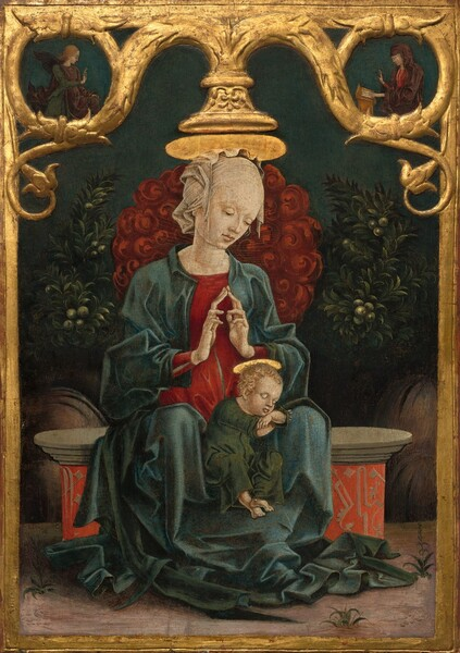 A woman sits facing us on a stone bench with her hands in prayer over the head of a golden-haired baby who sleeps, propped up between the woman's knees, in front of pine-green bushes and plants in this vertical painting on wood panel. The panel is framed by carved, curling gold vines encircling two small people in the upper corners. All the people have pale skin and plate-like, shiny gold halos seem to rest atop the woman and child's heads. The woman tilts her head to her left, our right, to look toward the baby with lowered eyes. Her skin is smooth and a translucent white cloth covers her head. She wears a berry-red dress under a teal-blue cloak that falls in folds over her arms and legs, and pools around her shins and feet. She steeples her elongated fingers to touch in front of her chest. The baby wears a forest-green robe and has bare feet. He rests his chin on crossed forearms, which rest on the woman's left leg, to our right. He has blond, curly hair and delicate features. The woman sits on a stone bench with a base decorated with tan designs against a vivid orange background. Tufts of grass grow in a few areas near her feet and the bench in the dirt ground. A cloud of crimson-red, swirling forms, perhaps blossoms, behind the woman is flanked to each side by leafy, dark green bushes bearing green, round fruit. In a roundel made by one gold, scrolling vine in the upper left is occupied by a winged angel facing our right in profile. The angel wears a plum-purple robe over a pine-green garment, and holds up the first two fingers of one hand, palm facing out. In the roundel in top right corner, a woman wearing a dark purple robe covering her head and body over a ruby-red dress sits facing our left in profile. She rests one hand on a book on a wooden desk in front of her and the other hand is raised, palm facing out. The background behind the small and central people is midnight blue.