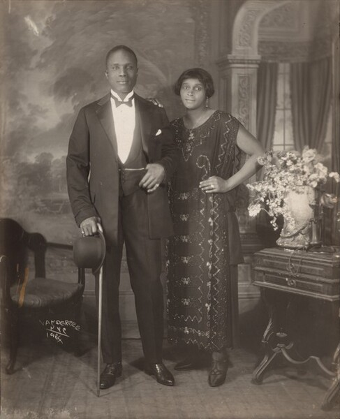 """An elegantly dressed Black man and woman stand facing and looking at us, slightly smiling, in a room in this vertical photograph. The image is monochromatic like a black and white photograph but is printed in warm tones of golden and dark browns. To our left, the man has short-cropped hair and is cleanshaven. He wears a three-piece tuxedo and holds a bowler hat and cane in his right hand, on our left. He pulls his suit jacket back to hook his opposite thumb in his vest pocket. He wears rings on each of his pinky fingers and a chain crosses his vest, tucked into the same pocket as his thumb. The woman stands with her left hand, on our right, on her hip and her opposite hand resting on the man's shoulder. She has a cheek-length bob haircut and wears dangling earrings and a necklace with a pendant. Her ankle-length, sleeveless dress is beaded with geometric and scrolling patterns. Some of the beads and the ring she wears on the fourth finger of the hand on her hip catch and reflect the light. An upholstered chair sits to our left and a wood side table with an urn filled with flowers and a telephone stands to our right. The telephone has a conical earpiece hanging from a stand with the flaring mouthpiece. The background behind the people has a painted or wallpapered section to our left and an arch leading to a curtained window to our right. Parts of the photograph are noticeably out of focus, particularly the background and flowers. The artist signed the work with white letters against the dark shadows under the seat of the chair, near the lower left corner: """"VAN DER ZEE NYC 1924."""""""