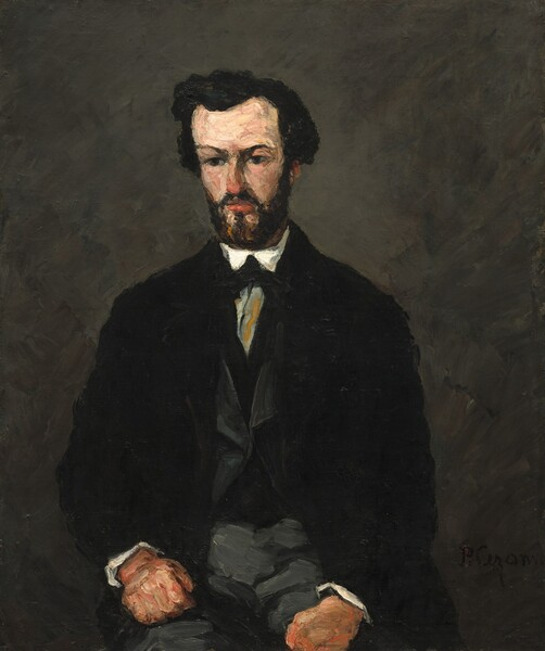 """A light-skinned man with thick black hair and a squared off black beard, dressed in a black jacket over a grey vest and grey trousers, sits facing us, with his brown eyes looking down and to our left in this vertical portrait. The top of the man's long head is considerably wider than his chin, making his head look a little too large for his body. The tip of his nose almost matches the coral red of his lips. Two pale peach patches below his mouth break up his beard. His hands, clenched into fists, rest on his thighs which are cut off by the bottom of the canvas. He wears several layers of clothing. The open black jacket reveals a grey vest with a V-shaped opening over a black sweater or undervest over a white shirt, which is visible as two bright triangles below his beard and as edges of white cuffs at his wrists. A long grey triangle pointing downward, streaked with tan, at the center of his chest and framed by the V-shaped opening of the undervest, could be a glimpse of his shirt or of a cravat. All the forms are rendered roughly, with broad, loose, layered, and intermingled brushstrokes, perhaps mixed together with a palette knife. The background is painted with grey strokes over black. The artist signed the painting in black paint in the lower right corner, though it is barely visible: """"P. Cezanne."""""""