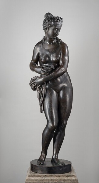 This bronze sculpture is of nude woman who reaches her left arm, on our right, across her body to hold a piece of drapery bunched at her opposite hip, while she holds a conch seashell in her other hand close by. In this photograph, her body faces us and she looks down and to our right. She has a straight nose and her full lips are closed. Her long, wavy hair is gathered into a knot at the top of her head, and a few tendrils trail down her neck and shoulders. Her sloping shoulders frame round breasts, which seem placed close together on her chest. Most of her weight is on her left leg, on our right, and her other knee is bent so she balances on the ball of that foot. With her hips swaying slightly to our right and her arms sweeping to our left, her body makes a gentle spiral that runs from head to toe. She stands on a round, disk-like plinth on a veined, tan marble base. Light glints off the polished, deep brown bronze surface of the sculpture.