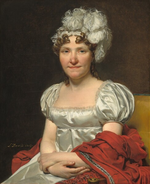 """Shown from the lap up, a woman with peachy skin, wearing a white silk dress and feathered headpiece, sits facing and looking at us in a harvest yellow upholstered chair in this vertical portrait. She has blue-gray eyes and a rounded, slightly pink nose. Her thin lips are closed and pulled back with shallow dimples at the corners of her mouth. Chestnut brown ringlets frame her face and fall to her shoulders under a white hat or headband covered with curling, billowing white feathers. Light reflecting off the cloth of her high-waisted dress suggests that it is silk or satin. It has a lace-lined square neckline and puffed short sleeves. She crosses her arms at the wrist and her hands rest in her lap, holding opposite forearms. A red shawl with silver and blue trims wraps over her left arm, on our right, and bunches up behind her against the yellow chair. The artist signed and dated the work in yellow paint against the dark background behind the woman: """"L. David 1813."""""""