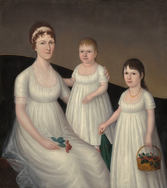 A woman and two children, aged about three and eight, wear nearly matching white dresses in this vertical portrait. All three have pale white skin. Their floor length, short-sleeved, scoop-necked dresses are made with what looks like light, tulle-like fabric gathered just below the bust. The woman sits to our left on a dark sofa. The back of the couch curves up over her shoulders and down to our right, and off the painting. The top edge of the sofa has nail-head trim and the wall behind it is elephant gray. The woman's curling brown hair is pulled back behind a white headband. She has gray eyes and her pink lips are closed. She holds a sprig of strawberries with her right hand, which rests in her lap. Her left arm, on our right, wraps around her younger daughter who stands on the sofa at the center of the composition. The child has blonde hair and light brown eyes, and wears a delicate, coral bead necklace. To our right, the older daughter stands in front of the couch. Her black hair is brushed back from her face except for bangs that sweep across her forehead. She has dark brown eyes and wears a gold colored necklace. The older girl holds a basket of strawberries with her left hand and rests her other hand on the pointed end of a parasol, which is tucked behind her body to our left. All three gaze out at the viewer.