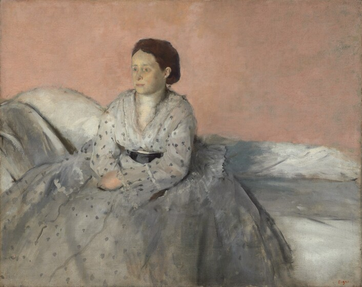 """Seen from about the ankles up, a woman with ghostly, pale skin, wearing a full, silvery-white dress with gray dots, sits on a low-backed white sofa against a salmon-pink background in this horizontal portrait painting. Just to our left of center, the woman sits with her body angled to our left and she looks in that direction with pale green eyes. Touches of green shade the inner corners of the eyes and her complexion has a yellowish cast. Her pink lips are closed and her chestnut brown hair is parted in the middle and pulled back. Her hands rest in her lap with wrists crossed. The dress darkens from eggshell white on the chest and sleeves to nickel gray on the skirt. Charcoal-gray dots, almost blurry around the edges, create an irregular pattern that becomes looser as it moves down the skirt. Her dress is cinched at the waist with a black sash. The skirt spreads over her settee, which has a low back and angles up on our left so that it could support a reclining person. The pale coral colored wall behind her takes up the top half of the composition. The painting is created blended brushstrokes, giving it a soft, almost hazy look. The artist's signature in red appears in the lower right corner: """"Degas."""""""