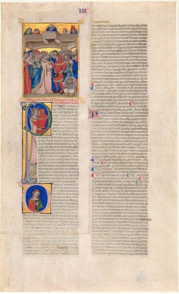 This long, vertical page of text in two columns is illustrated at the top left with a rectangular scene showing a crowd under a balcony over a large, capital P above a letter D, each letter framing a scene with people, painted on an oatmeal-colored sheet of vellum. The paintings on this illuminated manuscript page are primarily done with shades of tomato red, rose pink, bright, royal blue, pine green, and glimmering gold, and the densely spaced writing is black. All the people have pale skin. Most of the women wear crowns over long, braided hair and long dresses. The men wear tunics or robes. In the rectangular illustration at the top left, a crowd of more than a dozen people gather closely around a man wearing a scarlet-red tunic, hood, and stockings, putting a gold ring on the hand of a woman wearing a shell pink dress and translucent veil. Two men to our right blow long horns, a man in front of them bends over to strike a pair of drums, and a woman to our left plays an instrument like a violin. Five people peek over the edge of a balcony above the crowd in front of a shining gold background. Below this scene, within the round form of the letter P, the man in red and woman in pink are shown from the waist up, kissing and embracing against a vibrant blue background. In the D below, which resembles an O with an elongated apostrophe at the top, a woman with brown hair, wearing a garment that is half red and half green, holds a hand to her chest. The other hand rests on the bottom of the opening within the D. The tightly spaced text, next to the P and D, extends down to the bottom of the column and the right column is entirely text. About halfway down the right column, a capital P is picked out with blue against a red field, and marks in blue and red are interspersed in the text in that column. There is a wide margin surrounding the text around all four sides of the sheet. The roman numeral four, made of four Is, alternates red and blue Is at the top center.