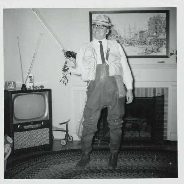 Untitled (Man in living room with fishing pole)