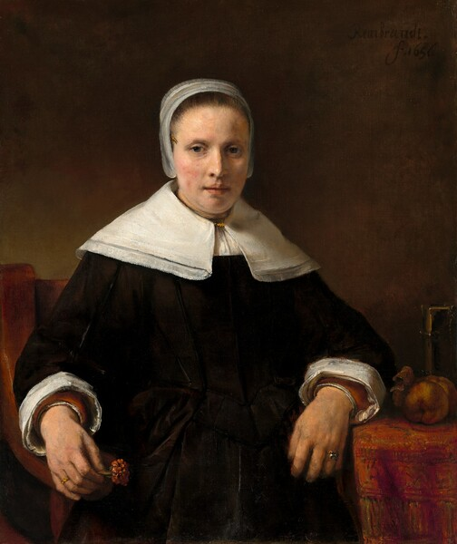 """Shown from the lap up against a dark background, a fair-skinned woman wearing a black dress looks out at us in this vertical portrait. Soft light coming from our left highlights her oval face, the peach blush on her cheeks, and her crisp white collar, cap, and cuffs. Her brown hair is pulled back under the cap that flares slightly over her ears and the wide, lace-trimmed collar covers her shoulders. She has dark eyes, a straight nose, and her pink lips are slightly parted. Her left arm, on our right, rests on a table covered with a rose-red patterned carpet next to two pieces of fruit, perhaps apples, and a book fastened with metal clasps. She rests her other arm on the arm of the wooden chair and holds a deep pink carnation the same color as the carpet. She wears a ring on the fourth finger of each hand. The artist signed the work with black paint against the dark background near the upper right corner: """"Rembrandt. f.1656."""""""