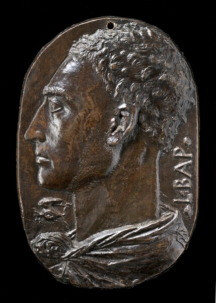 """This bronze oval medallion shows the profile of a man facing our left, his head and neck filling the space. He has short wavy hair and a long, pointed nose. He looks steadily into the distance to our left and his lips are closed. His garment wraps around the back of his neck and is knotted at the base of his throat. The capital letters """"L BAP"""" run vertically up near the edge of the medallion in the space behind his neck to our right. A symbol under his chin to our left is made up of a wing arched over a stylized eye. Light glints on the deep brown bronze surface, especially on the front of the chin, cheeks, and forehead, and in his choppy hair."""