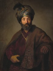 """Seen from the waist up, a dark complected white, bearded man wearing a turban and voluminous robes stares at us in this vertical portrait. Lit strongly from the left, the man's brow is slightly furrowed over brown eyes, and his gray beard is neatly trimmed. His turban is accented with a gold chain and feather, and his fur-lined robe is clasped over a burgundy red-garment with another gold chain. His right hand, on our left, grasps a sash that wraps around his waist, while his other hand rests on a wooden staff. The gray background behind the man deepens into shadows at the corner. The artist's signature is painted to our left near the man's upper arm. The first letter """"R"""" is missing so it reads """"embrandt ft."""""""