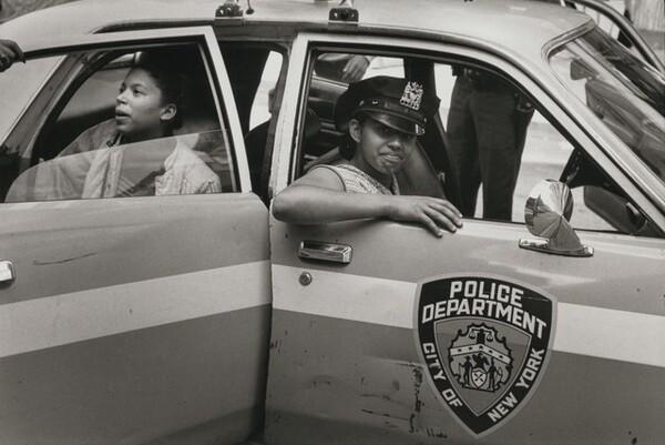 On a warm July day neighborhood children play in a patrol car, New York City