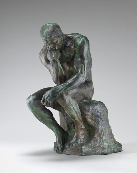 This free-standing bronze sculpture shows a nude, muscular man sitting on a rock and resting his chin on the back of his right hand, that elbow propped on his left knee. In this photograph, the man's body is angled slightly to our left. He hunches a bit as his body twists so his right elbow, on our left, reaches the opposite knee. His left arm, on our right, rests along his leg so the hand dangles beyond the knee. The man has short-cropped hair, a furrowed brow, an angular nose, and lines around his mouth and eyes. His left foot, on our right, rests higher on the rock so that knee juts up a little higher than the other. The bronze has a greenish patina, especially noticeable along the top of the man's head and shoulders and the front of his lower legs.