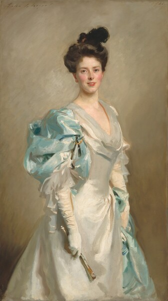 """Shown from the knees up, a young woman with a creamy complexion and flushed cheeks looks at us, wearing a long, shimmering white dress partially draped with powder blue fabric, is shown against a golden tan background in this vertical painting. The brushstrokes are loose, giving the entire portrait a soft, almost blurred look. Her dark, chestnut brown hair is piled loosely on her head. A dark form could be a feather or small hat. Her eyes may be two different colors; her right eye is blue and her right eye looks almost green. She has a straight, snub nose and her fuchsia pink lips are open in a small smile. There is a faint suggestion of a cleft in her pointed chin. Her white dress has a low, scooped neck and a tight-fitting bodice over a flaring skirt. Her body is angled to our right so we see the powder blue fabric, possibly pinned or pulled through a gold ring on her right shoulder, closer to us. The blue fabric appears on her left hip, farther from us, suggesting that it wraps around her back and perhaps creates a train. The sheen of the white dress and powder blue train suggests silk. The artist signed the work in cursive letters in the upper left, """"John S. Sargent,"""" and dated it in the upper right, """"1902."""""""