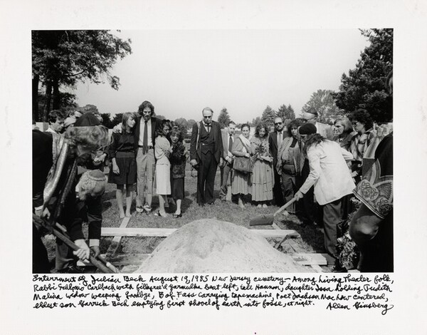 Internment of Julian Beck August 19, 1985 New Jersey cemetery—Among Living Theater folk Rabbi Schlomo Carlebach with filigreed yarmulke front left, tall Hanon, daughter Isha holding Judith Malina widow weeping goodbye, Bob Foss carrying tape machine, Poet Jackson Machour centered, eldest son Garrick Beck emptying first shovel of earth into fosse, at right.
