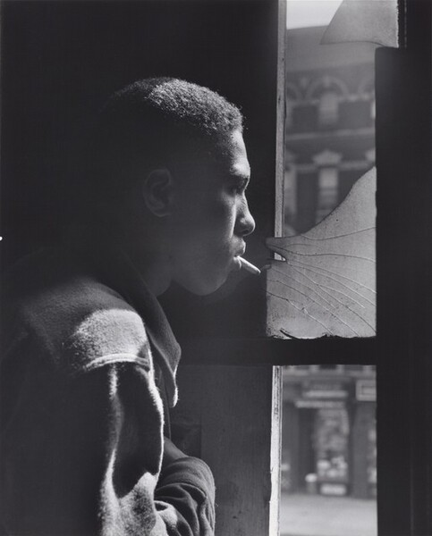 A young Black man stands in profile looking out a tall window to our right in this vertical black and white photograph. The image is cropped so his head, shoulder, and upper arm fill the left half of the composition. He has short hair and wears a shirt or jacket that diffuses the light to suggest that it could be flannel or another soft fabric. With a cigarette dangling loosely from his lips, he stares through the shattered upper pane of the window and he holds his right hand across his chest. The strong light source from the right accentuates his nose, cheeks, hair, and shoulder, and the space behind him is lost in shadow. A blurred, three-story building across the street has a dark façade with white stone lintels above the windows and a mansard roof with curved dormers.