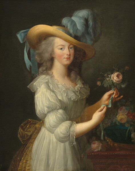 Seen from about the hips up against a dark gray background, a rosy-cheeked, light-skinned woman stands before a wooden table as she arranges flowers in this vertical portrait. Her body is angled towards our right and she turns to look at us with clear blue eyes under curving brows. She has a straight nose and her small bow lips are closed. Her gray hair is loosely bound and curls fall over her shoulders. She wears a white muslin dress with puffed sleeves and blousy ruffles around the neckline. Her dress is gathered at her waist with a sheer gold, striped sash. The wide brim of the woman's straw hat curves down across her forehead, and a robin's egg-blue ribbon is tied around the crown into a bow at the back. Puffy feathers of the same color blue billow up and forward at the front of the hat. She stands at a wooden table that extends off the right side of the canvas. A deep blue bowl sitting on bright gold feet holds pale pink, yellow, crimson, and aquamarine blue flowers. The woman holds up a pink flower, perhaps a rose, in her left hand and ties it with a blue ribbon.