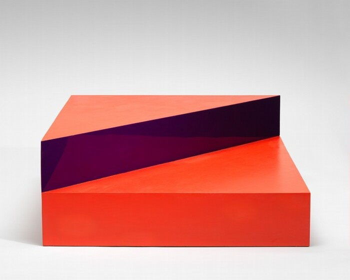 This abstract sculpture is made up of a square, scarlet-red box like a platform topped with a triangle, half the size of the square. In this photograph, we look onto one side of the square base, and the triangle lines up with the half farther from us. The front face of the triangle is a reflective, amethyst purple surface that reflects the square box beneath and the top surface appears to be coral orange. The backdrop behind the sculpture fades from light gray along the top of the photograph to white along the bottom.