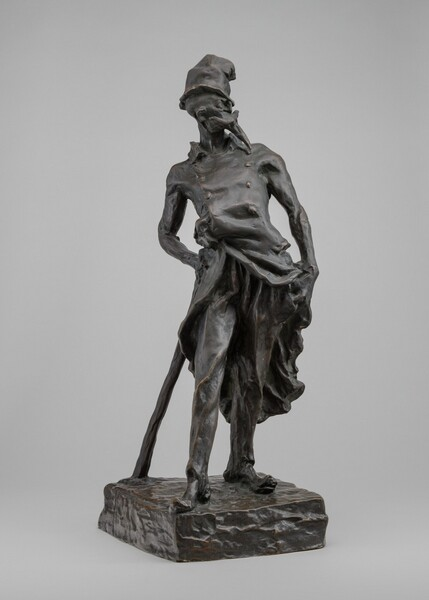 This bronze sculpture shows a thin man wearing a tall, crumpled hat, an ill-fitting coat, and worn shoes, standing and leaning on a long cudgel resembling a cane. His body faces us in this photograph and he looks over his shoulder to our right in profile. His goatee is so exaggerated that it creates a beak-like form reaching almost to his chest beneath an upwards sweeping mustache that is wider than his face. He has a wide, blade-like nose and bulging eyes, and we get the impression that he might be bald. The top of his tall hat seems to have been crushed and it curves away from us. His double-breasted, knee-length coat has a high collar and it sweeps open over his hips. His left hand, on our right, holds the coat open so he can get to his pants pocket. He holds and leans onto the long cudgel on our left so his hips sway to our right. His long pants cover thin legs, and his toes poke through the front of his tattered shoes. The low, square base he stands on is textured as if roughly modeled before being cast.