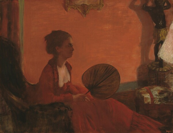 Dominated by tones of red and fire orange, this nearly square painting shows a seated woman leaning forward in a high-backed chair, holding a round, flat, leaf-shaped fan. She sits to our left facing our right in profile, so the back of the chair is cropped by the edge of the composition. The coral red wall behind the woman spans the width of the painting and the skirt of her long ruby-red dress extends almost to the bottom right corner of the canvas. Her brown hair is pulled up and her face is in shadow. The flat disk of the fan rests on its edge on her lap, almost at the center of this painting. A few objects cropped by the right edge of the painting break up the suffused red palette, including a black sculpture of a person with arms raised overhead, a footstool, and a triangular white form, perhaps a lamp shade.