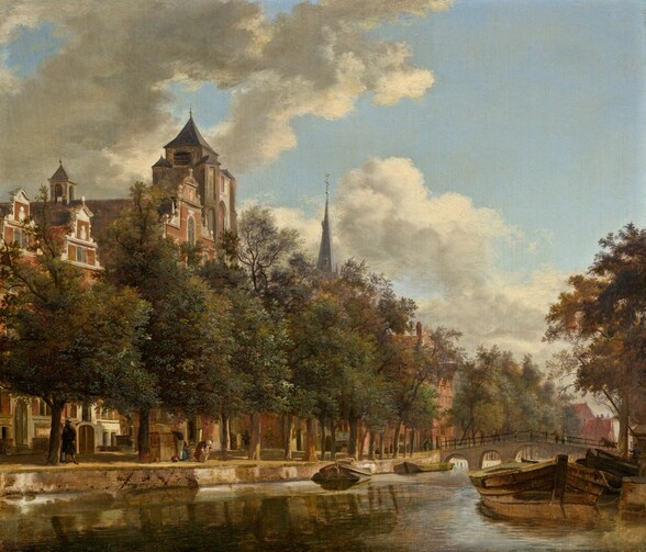 """As if from a boat or on a low bridge over a canal, we look across a sunny waterway to the opposite bank, where a row of tall, leafy trees partially blocks our view of red brick buildings and rowhouses with white stone trim in this horizontal landscape painting. The opposite bank angles from the lower left corner into the distance to our right, where it meets the horizon line near the right edge of the panel, about a fifth of the way up the composition.  The water in front of us ripples gently, reflecting the ivory-colored clouds and pale blue sky, the low barges or boats tied up along the edge of both sides of the canal, and the moss-green of the trees. Tiny in scale, a few people walk and work under the trees along the opposite bank. The building closest to us, to our left, has a stepped roofline and a peaked roof on a tall cupola. The stone-gray spire of a church pokes above the trees farther down the canal, and more red brick buildings are visible in the gaps between the tree trunks. More people and a horse cross a low, arched bridge spanning the canal in the distance to our right. The artist signed the painting as if he had inscribed his initials as a monogram on the boat closest to us to our right, """"IVH."""""""