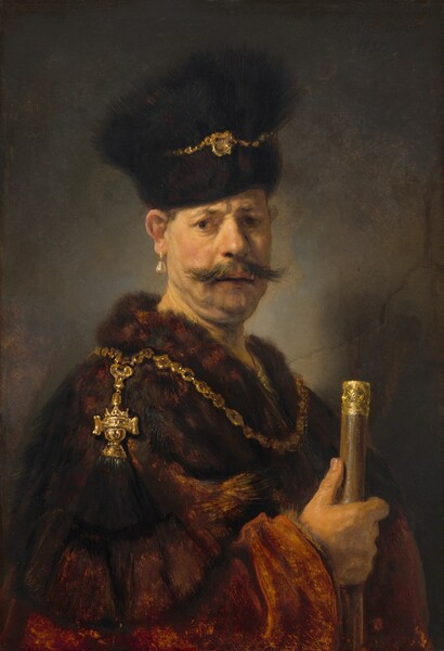 Shown from about the waist up, a light-skinned man with sagging jowls and a double chin wears a fur garment and hat, a large teardrop pearl earring, and gold chains, and he holds a gold-headed cane in this vertical portrait. In front of a cracked gray stone wall, the man stands with his body angled to our right but he turns to look at or towards us with brown eyes under a furrowed brow. He has a bulbous nose and his lips are slightly parted under a wide, wispy mustache. His brown hair is mostly hidden under the tall dark brown fur hat, which is wrapped with a gold chain with a gold medallion at the front. The chestnut brown fur coat looks especially fuzzy along the neckline, which is also encircled with a thick gold chain. A gold crown-shaped pendant with a black brush hangs over his right shoulder, closer to us. He holds a gold-tipped cane with his right hand, his thumb extended along the cane.