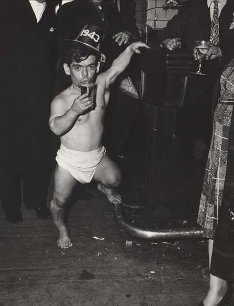 This vertical, black and white photograph focuses on a dark-haired, barefoot man of short stature wearing a diaper and party hat, which bears the year, 1943. His left hand reaches overhead and rests on a bar, his left foot perches on the footrail, and he holds a full glass to his pursed lips. He is surrounded by a black field, which eventually becomes evident as people wearing dark suits, their heads cropped by the top edge of the image.
