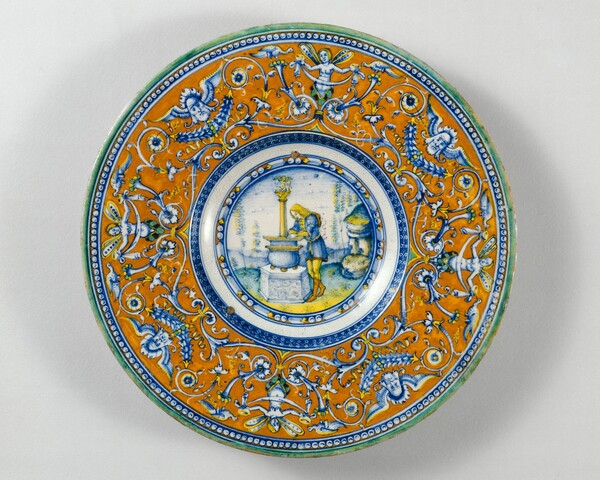 Plate with border of grotesques on an orange ground; in the center, Narcissus gazing at his reflection in a fountain