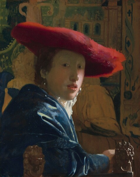 Shown from the elbows up, a young person with pale skin and brown hair wearing a wide, scarlet-red hat sits in front of a tapestry in this vertical portrait painting. She sits with her body facing our right in profile but she turns her face to look at or towards us from dark eyes. She has a rounded nose, rather flat cheeks, and a sliver of teeth is visible through parted coral-pink lips. The wide brim of the red hat seems to be made of a soft, almost feathery material, and it casts a shadow across her face. She wears a high-collared white garment that catches the light, a royal blue, possibly velvet robe or overcoat, and large, teardrop pearl earrings. Her arm runs along the bottom edge of the panel in front of two carved wooden lion finials that could be the arm or back of the chair. The tapestry behind her is painted in tones of pale caramel brown and pine green. The painting has a soft, hazy look and light glints with bright white specks off the pearl earrings, the tip of her nose, her lips, and the lion finials.