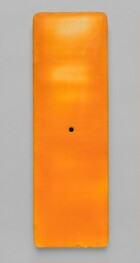 This rectangular, tangerine orange panel has rounded corners and a black dot at dead center. It hangs on a dove gray wall and is about three times as tall as it is wide. The surface turns a golden yellow where light reflects off some areas of the wax, especially in the top half.