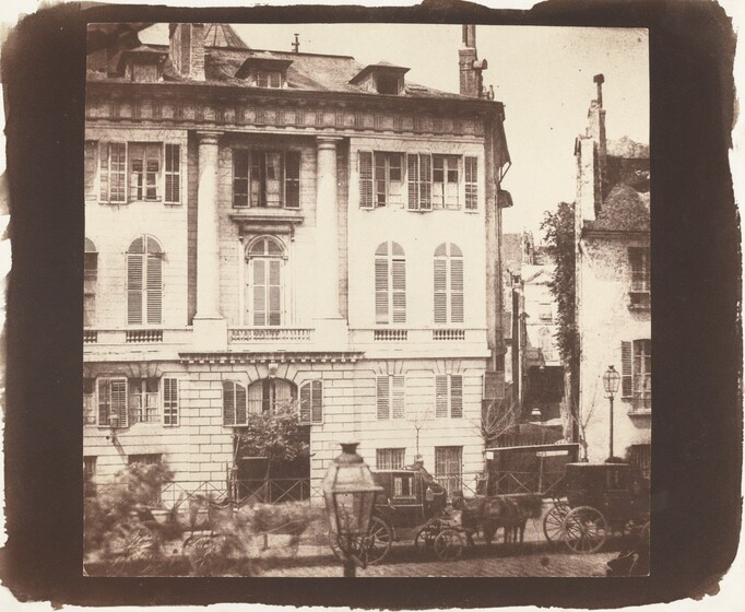 We look at the façade of a five-story building with a pitched roof as if from a building across the street in this square sepia photograph. Vertical rectangular windows are spaced along the lowest two levels of the building, which appears to be constructed with large rectangular stones. There is a squat, arched window over a dark opening at the bottom center. The façade of the next two stories is smooth. Tall, narrow arched windows line the third story and the fourth story has smaller rectangular windows with shutters. Columns frame the central bank of windows in the third and fourth stories. Dormers of the fifth level protrude from the low pitched roof, which nearly reaches the top edge of the photograph. Another house is visible through a narrow alleyway to our right and another shorter house is cropped by the right edge. Some details of the three horse-drawn carriages lining the street in front of the houses are blurry. The image is surrounded by a wide black band with uneven edges.