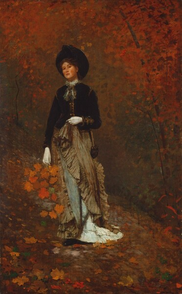 A woman with smooth, pale skin and wearing a hat, long dress, and gloves, stands holding a bunch of pumpkin-orange leaves against a background of trees painted with touches of rust orange and pine green in this vertical painting. The woman tips her head back slightly to look at us with dark eyes under arched eyebrows. Her cheeks are flushed and her coral-pink lips closed. Her round black hat perches on the back of her head and she has an inky black, long-sleeved, hip-length jacket with bronze trim at the shoulders, cuffs, and down the front. A gauzy bow is tied at her neck. Her left elbow, on our right, is bent and she holds up her tan-colored, ruffled skirt with a white-gloved hand. The raised skirt exposes sky-blue lining and white, ruffled flounces at her feet. Her right arm, on our left, hangs at her side and holds what seems to be the handle of a basket. Deep, marigold-orange leaves cascade out of the basket. One black shoe peeks out from under her long skirt. She stands on a hill carpeted with crimson-red, tawny brown, golden-yellow, and forest-green leaves. The space behind her is filled with touches and dabs of red, orange, brown, black, and tan to indicate trees in autumn.