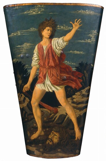 This shield shaped painting shows David, a fair-faced, dark eyed young man with curling brown hair, standing astride the severed head of a man with dark hair and swarthy skin. The painting is wider at the top and tapers like a long drinking glass to a narrower base. David holds the end of long red slingshot with his right hand. The slingshot is weighted by a rock and swings behind his body. His sleeveless orange-red garment is cinched at his waist over a long white shirt. Both garments skim David's thighs and his legs and feet are bare. Long, curling brown hair frames the ashen and bloodied upturned face of Goliath at David's feet. A palm-sized stone is embedded in his forehead. The landscape background is made up of gray boulders, a meandering river, and low palm-like trees. Frothy white clouds sweep across an azure blue sky from our left.