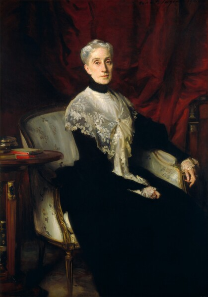 """A woman with pale skin, wearing a sheer, lace shawl over a high-necked, ink-black dress sits in an upholstered chair in front of a dark, cranberry-red curtain in this vertical portrait painting. The chair and her body nearly fill the composition, though her feet may be cropped by the bottom edge. She sits angled to our right but she turns her face to look at us with gray eyes under arched brows. Shadows line the creases above her eyelids. Set in her thin, oval face, she has a long nose, high cheekbones, and her coral-red lips are closed in a straight line. She is lit from our left, and the light glints in her silvery-gray hair, which is pulled up and back. Her velvety-black, long dress seems to have puffed upper arms over long sleeves that end with wide lace cuffs. The lace shawl wrapped around her shoulders is fasted with a pin at her chest, and the ends fall into her lap near her right hand, closer to us. The opposite arm rests along the arm of the low-backed chair so her long, elegant fingers dangle off the end. She wears a ring on each hand, including one glinting turquoise, perhaps indicating that it is a black or dark stone, and one with a pearl. The fabric on the chair is loosely painted tan-colored floral design against oyster white. A small, wooden table with a round top to our left, near her right elbow, holds a book with a sage-green cover and vivid red edges to the pages, and a shiny, round box. Barely visible against the red curtain behind the woman in the upper right corner is the artist's signature and date: """"John S. Sargent 1901."""""""
