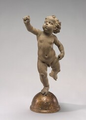 Sculpted in clay, a toddler balances his plump body on his right foot as he raises his left leg and right arm. His left hand, on our right, rests near his hip. Gazing up and to our left, his cheeks are puffed as if blowing through pursed lips, and his hair falls in soft ringlets. The fingers of his raised hand are folded into a loose fist. Tipped slightly forward onto his toes, he balances on a gold-half dome.