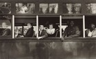 This horizontal black and white photograph captures the exterior of a trolley car cropped to show only the mid-section with six passengers inside.The passengers look out of five windows on the left side of the trolley, so their bodies face our left in profile. The four people at the front end, to our left, are white; two people at the back, to our right, are Black. From left to right: a man looks out through the glass of the closed window along the left edge of the photograph. The remaining windows are open. An older woman wearing a dark coat looks at us from under arched eyebrows, lips pursed, out of the next window, to our right. Two children—a boy of about eight and a girl of about two—look out of the central window. Closer inspection reveals the dark form of their caregiver lost in the shadowy interior of the trolley. A Black man wearing a long-sleeved, button-down shirt leans onto the window ledge with both forearms in the next window, and a woman wearing glasses looks over her shoulder, up and away from us in the right-most window, which is cropped by the edge of the photograph. The scene behind the photographer is reflected in glass panes above the seats on the exterior of the trolley.