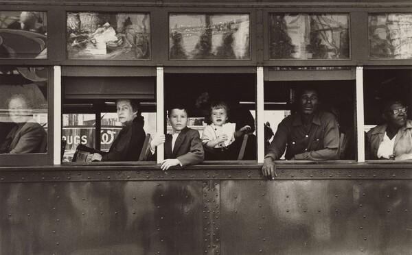 This horizontal black and white photograph captures the exterior of a trolley car cropped to show only the mid-section with six passengers inside. The passengers look out of five windows on the left side of the trolley, so their bodies face our left in profile. The four people at the front end, to our left, are white; two people at the back, to our right, are Black. From left to right: a man looks out through the glass of the closed window along the left edge of the photograph. The remaining windows are open. An older woman wearing a dark coat looks at us from under arched eyebrows, lips pursed, out of the next window, to our right. Two children—a boy of about eight and a girl of about two—look out of the central window. Closer inspection reveals the dark form of their caregiver lost in the shadowy interior of the trolley. A Black man wearing a long-sleeved, button-down shirt leans onto the window ledge with both forearms in the next window, and a woman wearing glasses looks over her shoulder, up and away from us in the right-most window, which is cropped by the edge of the photograph. The scene behind the photographer is reflected in glass panes above the seats on the exterior of the trolley.