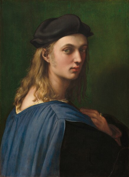 A young man with smooth, pale white skin and long blonde hair looks over his right shoulder at us in this vertical portrait. He has pale green eyes, a straight nose, full pink lips, and a narrow chin. His hair falls over his shoulders and a long sideburn reaches to his jawline on the side facing us. Shown against a background of emerald green, he wears a black floppy cap and a blue garment that splits over his shoulder. A ruffle of white is visible at the wide neckline and the sleeve of his right arm, which faces us, is black. He holds his left hand, farther away from us, to his chest and he wears a gold ring with a green stone on his pointer finger.