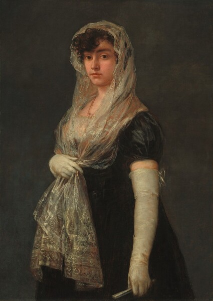 "Shown from the knees up against a dark gray background, a young woman with pale skin stands with her body angled to our left and she looks directly at us with brown eyes in this vertical portrait painting. She has dark, arched brows, a straight nose, and her full, coral-pink lips are closed. Her dark brown, curly hair is covered by a mantilla, an ivory-white, lacy scarf highlighted with pale gold and subtle, russet red highlights that she holds with her right hand, farther from us, below her bust. The ends of the scarf fall to mid-thigh over her ink-black, long dress. The bust of her dress is made from the same or similar shimmering material of the mantilla. Long, tight-fitting, off-white gloves nearly reach the short, puffed, cap sleeves of the dress. The back of the glove on her left arm, closer to her, is tied at the top with a bow, and she holds a silvery-white, closed fan in that hand. A brownish-coral colored necklace is painted as a squiggle of paint around her neck. Barely visible, the painter signed the painting in the lower left: ""Goya."""
