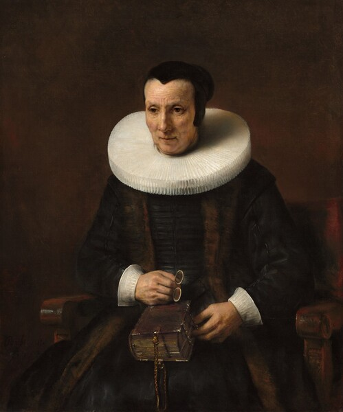 Seen from the knees up, a light-skinned woman wearing a black dress with white cuffs and a wide, starched collar sits in a wooden chair against a dark brown background in this vertical portrait. Her body faces us and she looks off to our left with brown eyes. She has slight jowls at her chin and her eyes, mouth, and forehead are lined. Her hair is pulled back under a close-fitting black cap. Extending straight from around her neck, her white collar is pleated into narrow figure-eights and nearly reaches her shoulders. She wears a brown stole over her velvety black dress, and both nearly blend with the dark background. She holds a pair of pince-nez spectacles in her right hand, which rests on a thick book in her lap. The spine faces her right and the opposite edge is fastened with metal clasps. A braided cord, perhaps leather, affixed to the narrow end of the book near us creates a loop.